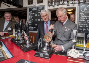 HRH pulls a pint of Greene King IPA at the White Horse, Upton